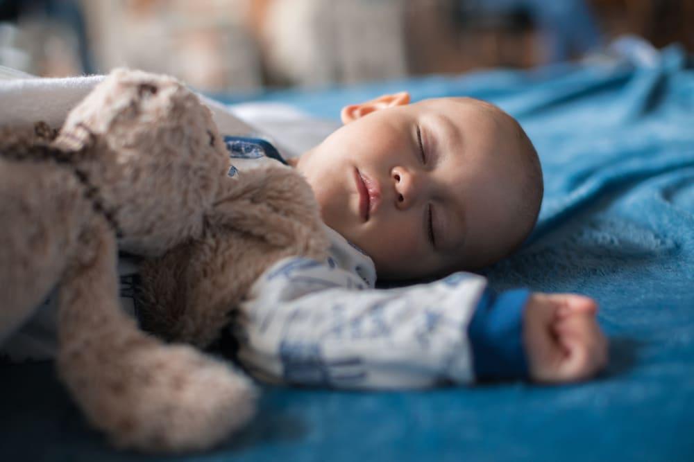Schlafender Junge mit Teddy